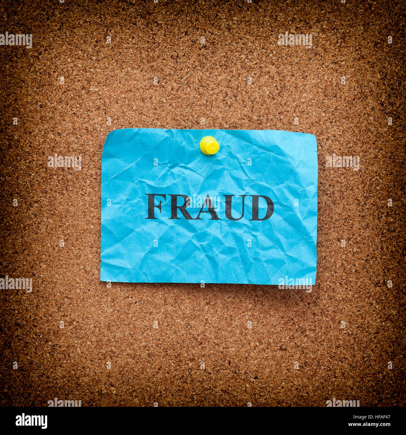 Il concetto di frode. Crumpled carta blu nota con il termine frode sulla bacheca di sughero. Vignetta. Close up. Immagini Stock