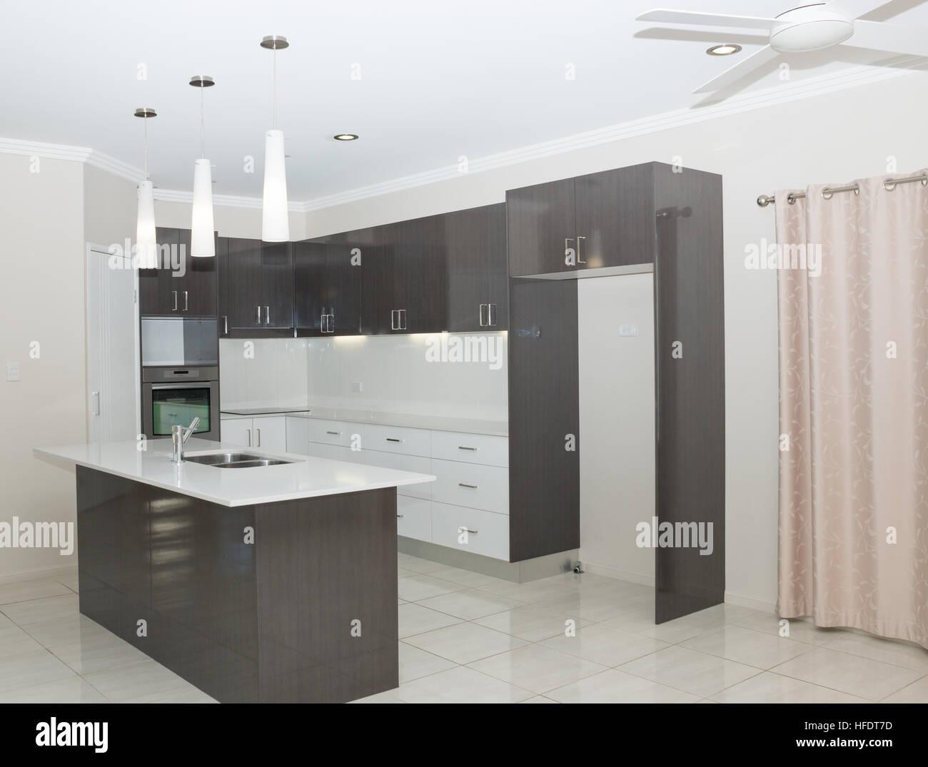 Nuova cucina moderna con isola da banco e luci pendenti foto