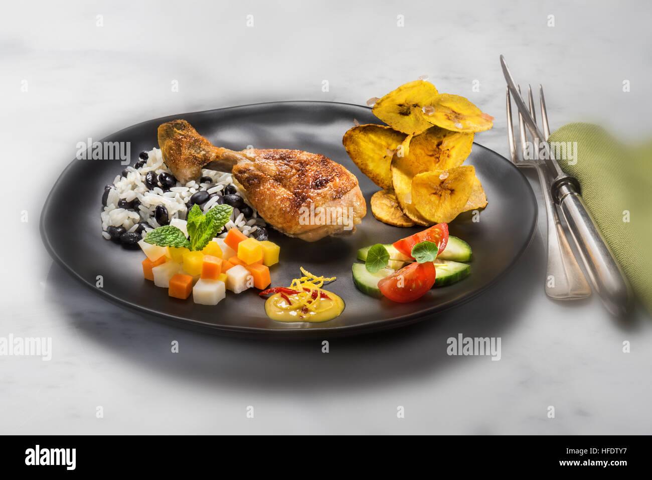 Tipico cibo cubano, pollo, riso con i fagioli neri, fritti banana chips, insalata e verdure. CUBA. kuba stile alimentare Immagini Stock