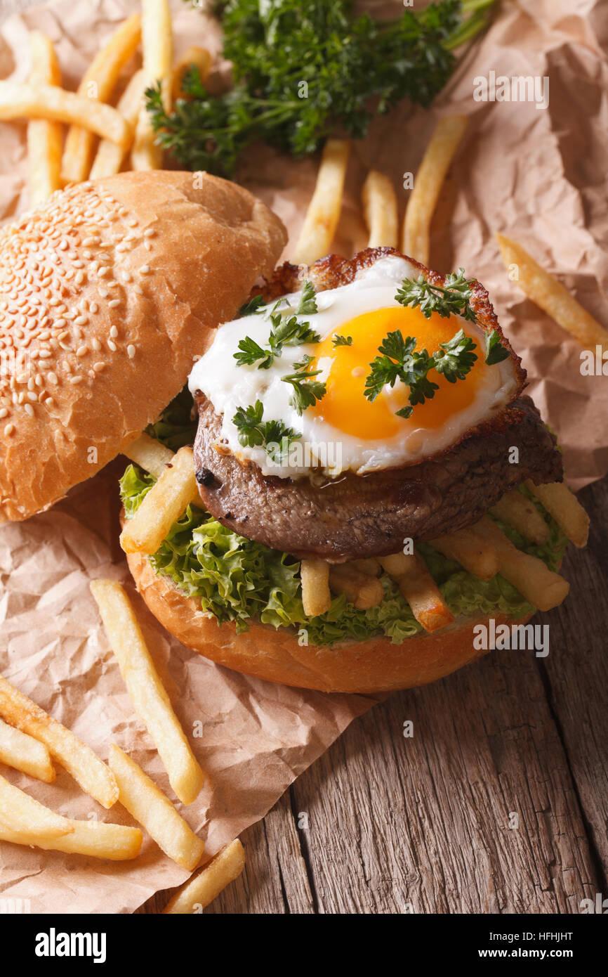 Sandwich rustico con bistecca di manzo, uova fritte e patatine fritte verticale. Foto Stock