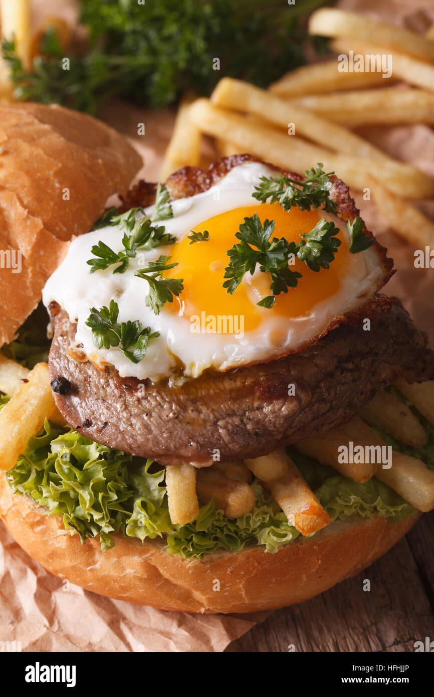 Sandwich con bistecca di manzo, uova fritte e patatine fritte close-up verticale. Immagini Stock