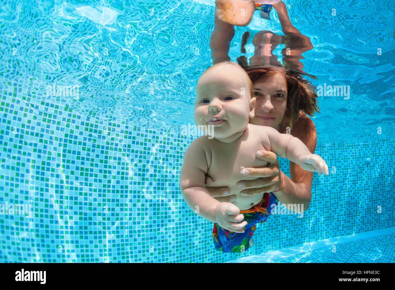 Famiglia fitness. padre tenere in mani baby figlio di apprendimento subacquea immersioni in piscina. Uno stile di Immagini Stock