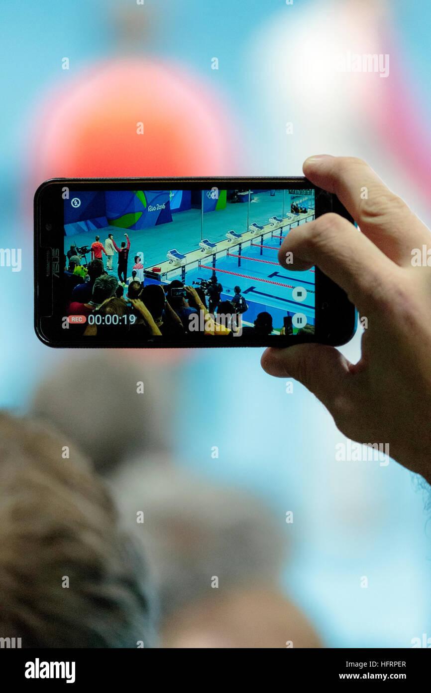 Rio de Janeiro, Brasile. Il 9 agosto 2016. Spettatore utilizzando il telefono cellulare per fotografia Michael Phelps Immagini Stock