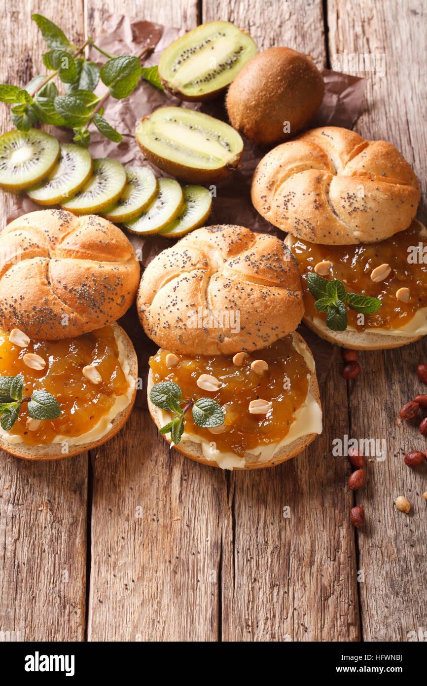 Panini dolci con burro e marmellata di kiwi e arachide vicino sul tavolo. In verticale Immagini Stock