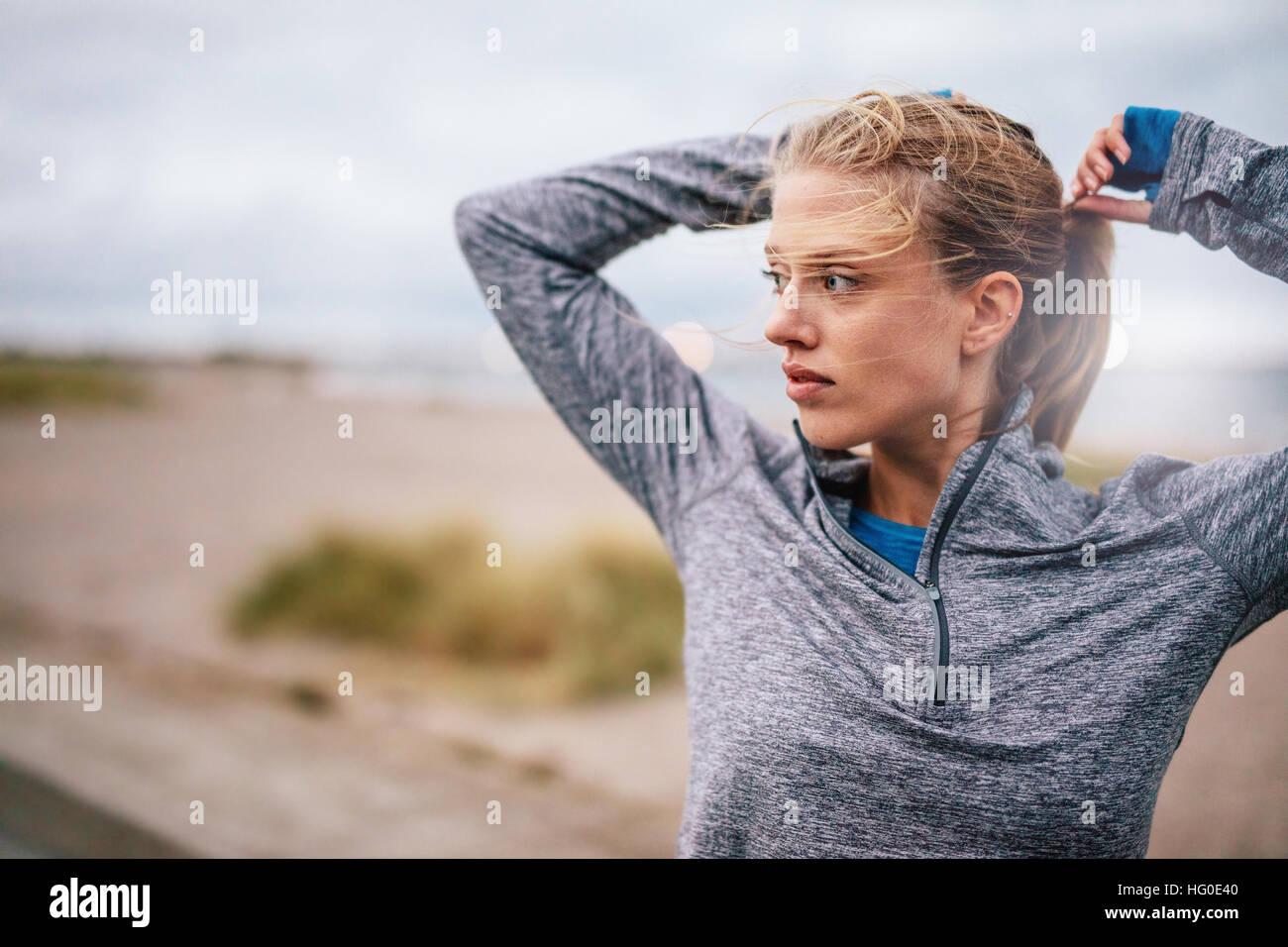Chiusura del giovane femmina runner occupare capelli prima di un'esecuzione. Sportivo da donna fitness su allenamento Foto Stock