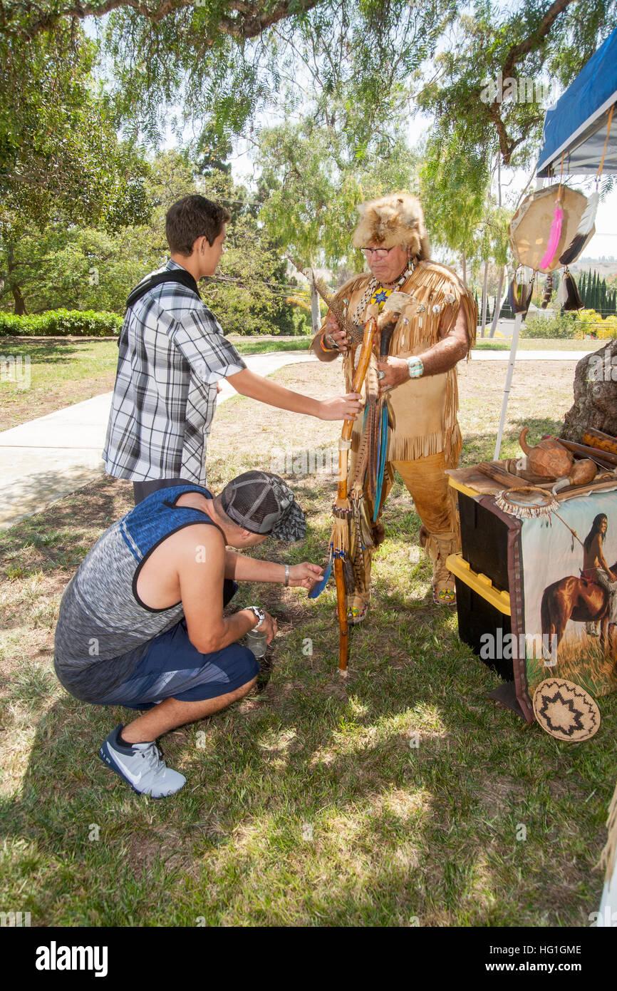 Vestito come un vecchio tempo Nativo Americano indiano di missione, una storica ri-enactor spiega manufatti storici Immagini Stock