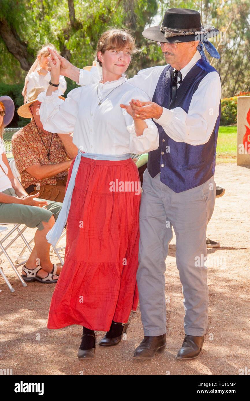 Vestito come old time Californians spagnola, un insegnante di danza e studente di eseguire uno storico stile coloniale Immagini Stock