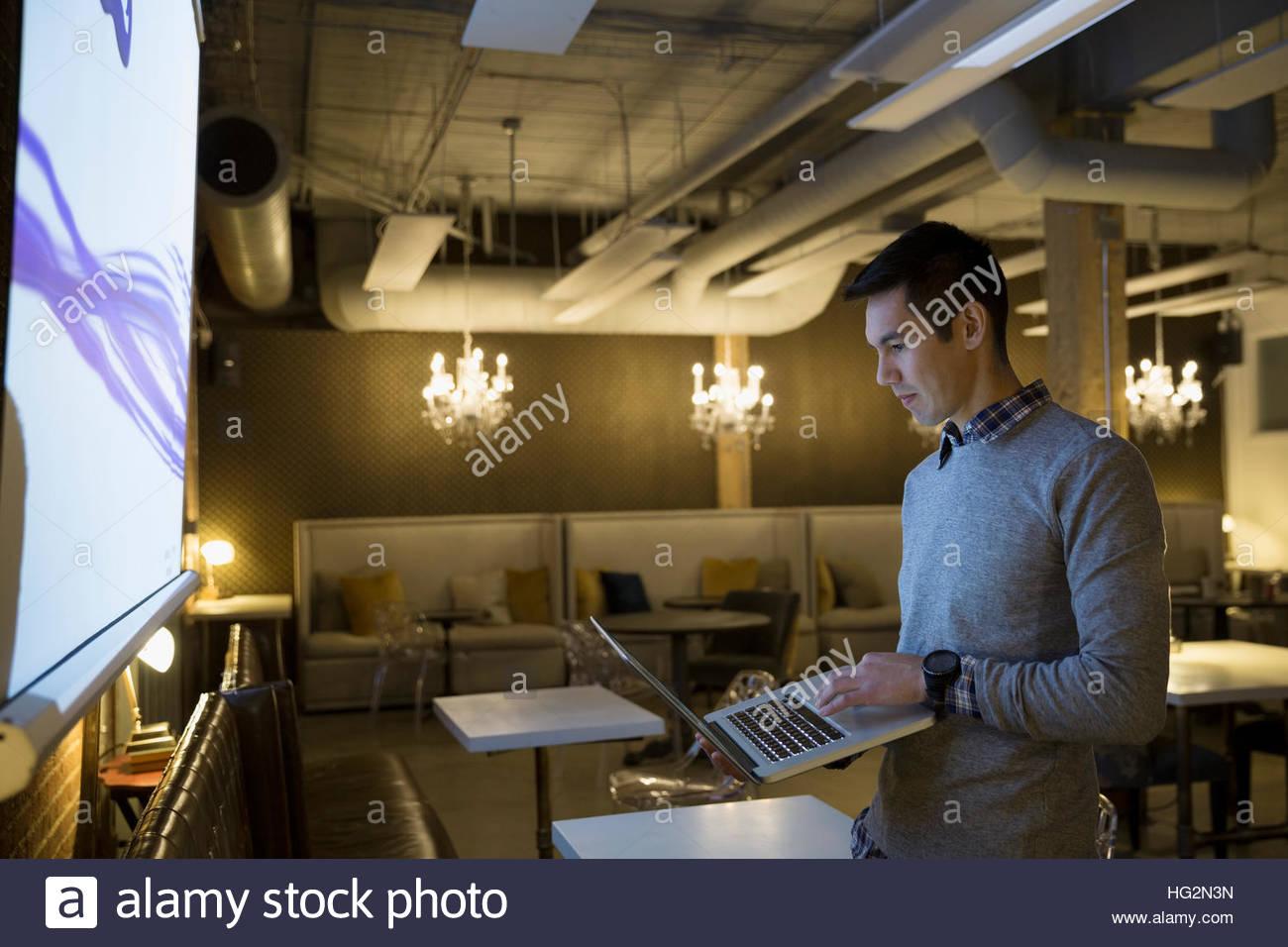 Imprenditore focalizzato utilizzando laptop preparazione presentazione audio visiva in office Immagini Stock