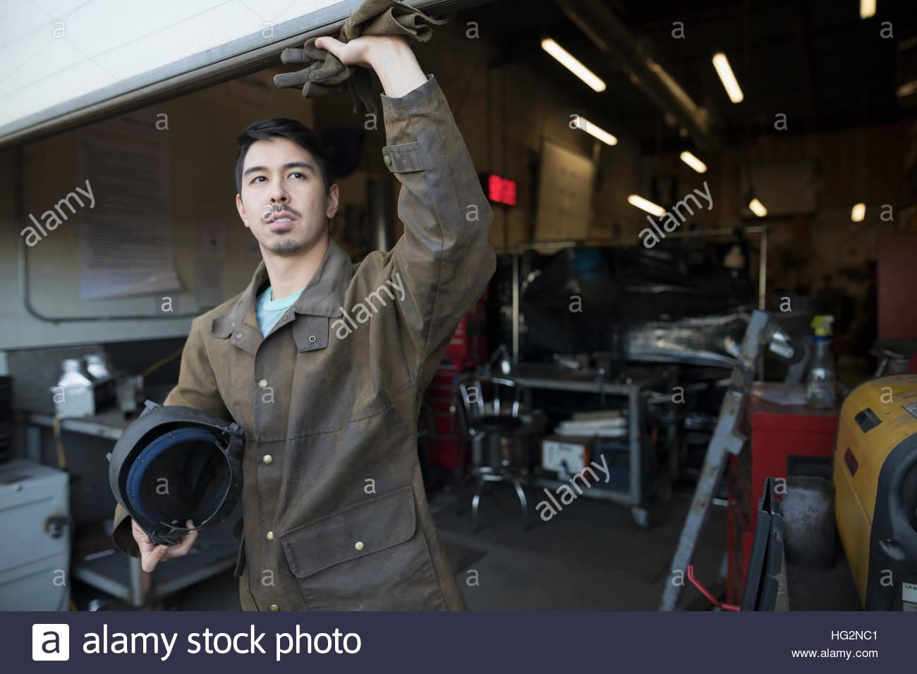 Saldatore maschio in piedi in officina porta Immagini Stock