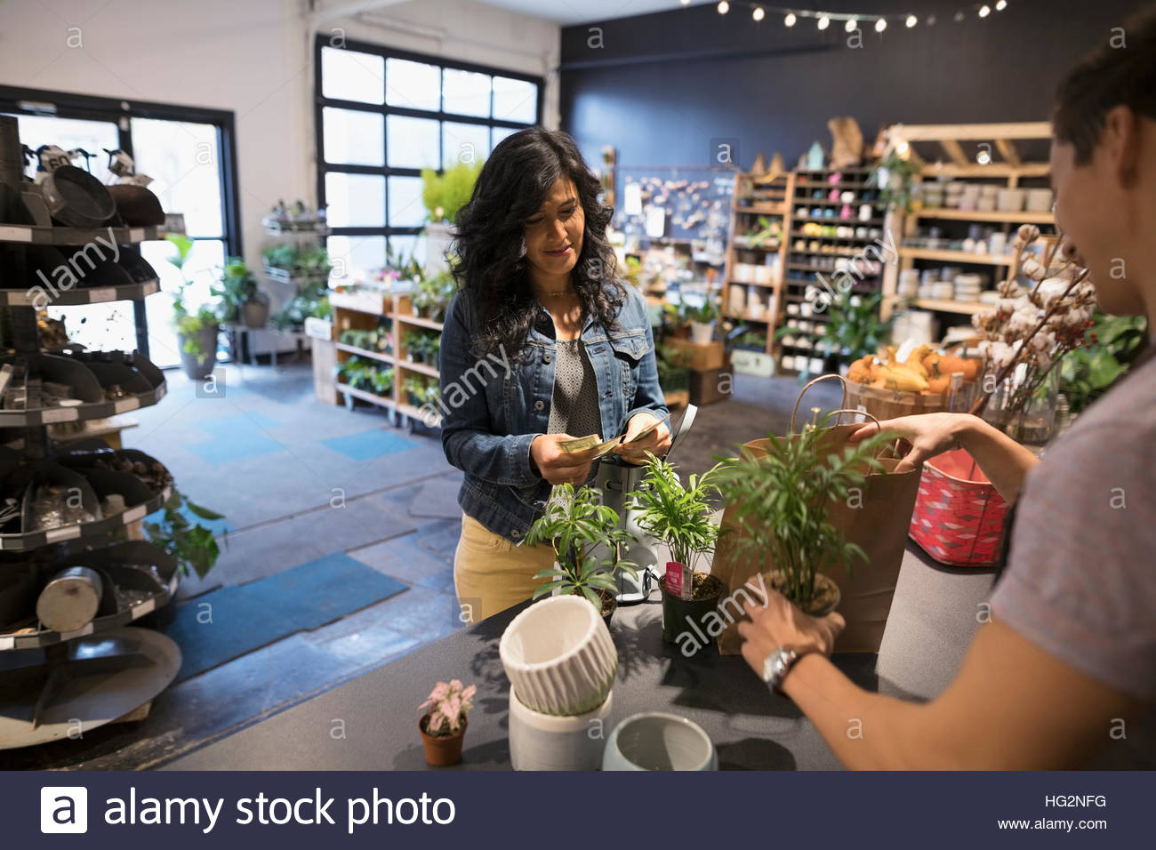 Maschio di proprietario di un negozio di aiutare il cliente femmina acquisto di impianti in negozio Immagini Stock