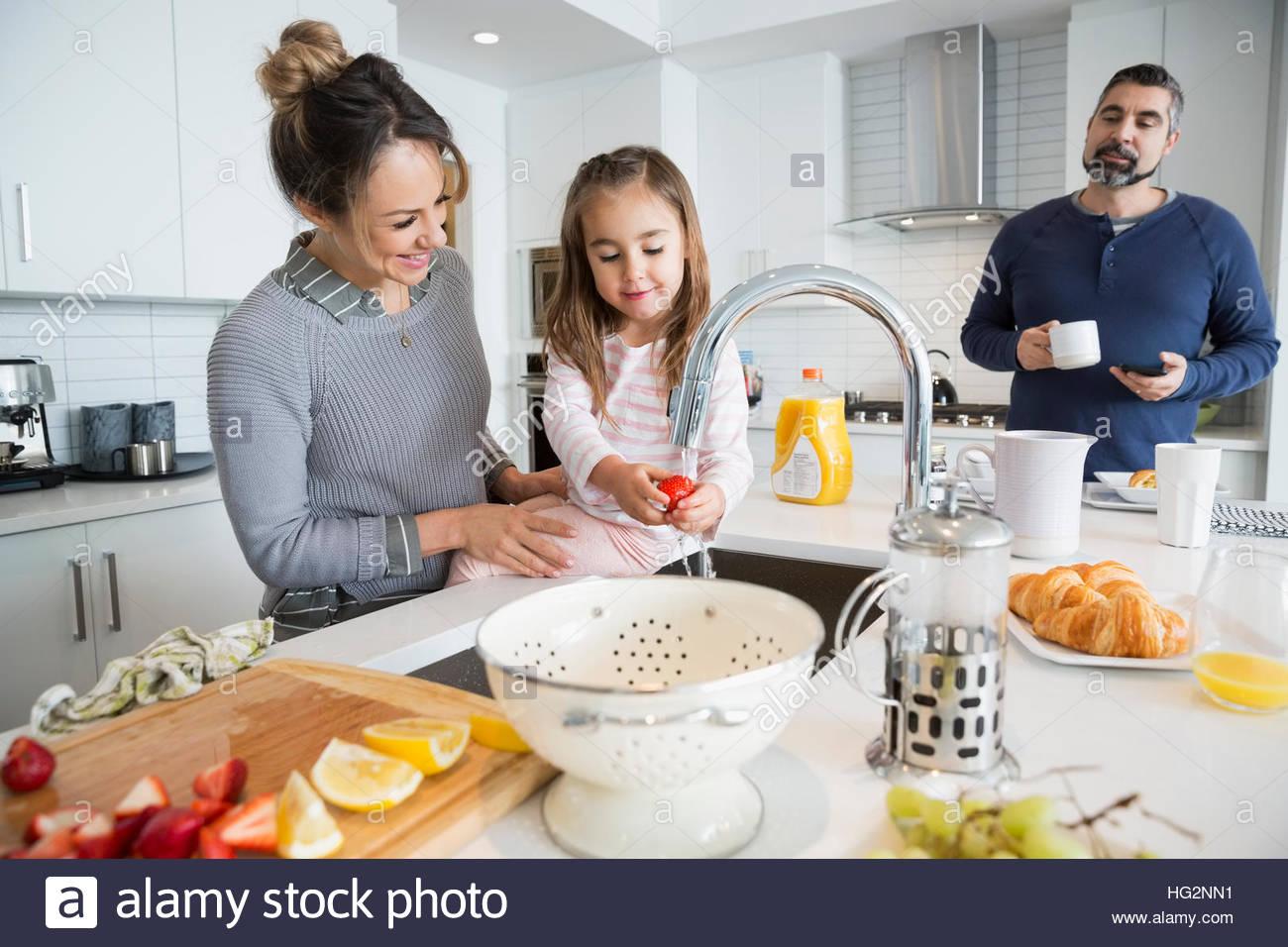 Figlia di madre aiuta il lavaggio di frutta nella cucina di mattina Immagini Stock