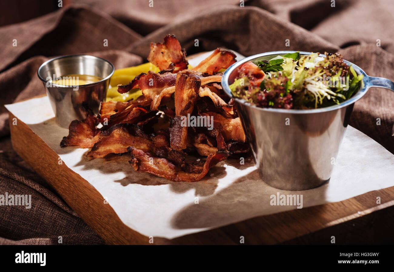 Insalata e fritti gustosi bacon in piedi su un vassoio in legno Immagini Stock