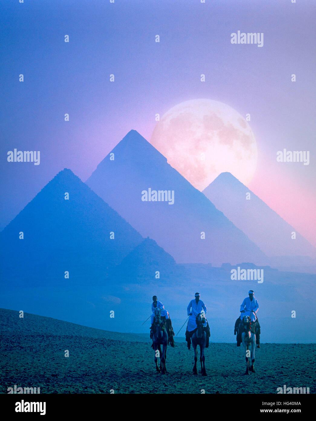 La luna piena sorge dietro le piramidi al tramonto, Giza, il Cairo, Egitto Immagini Stock