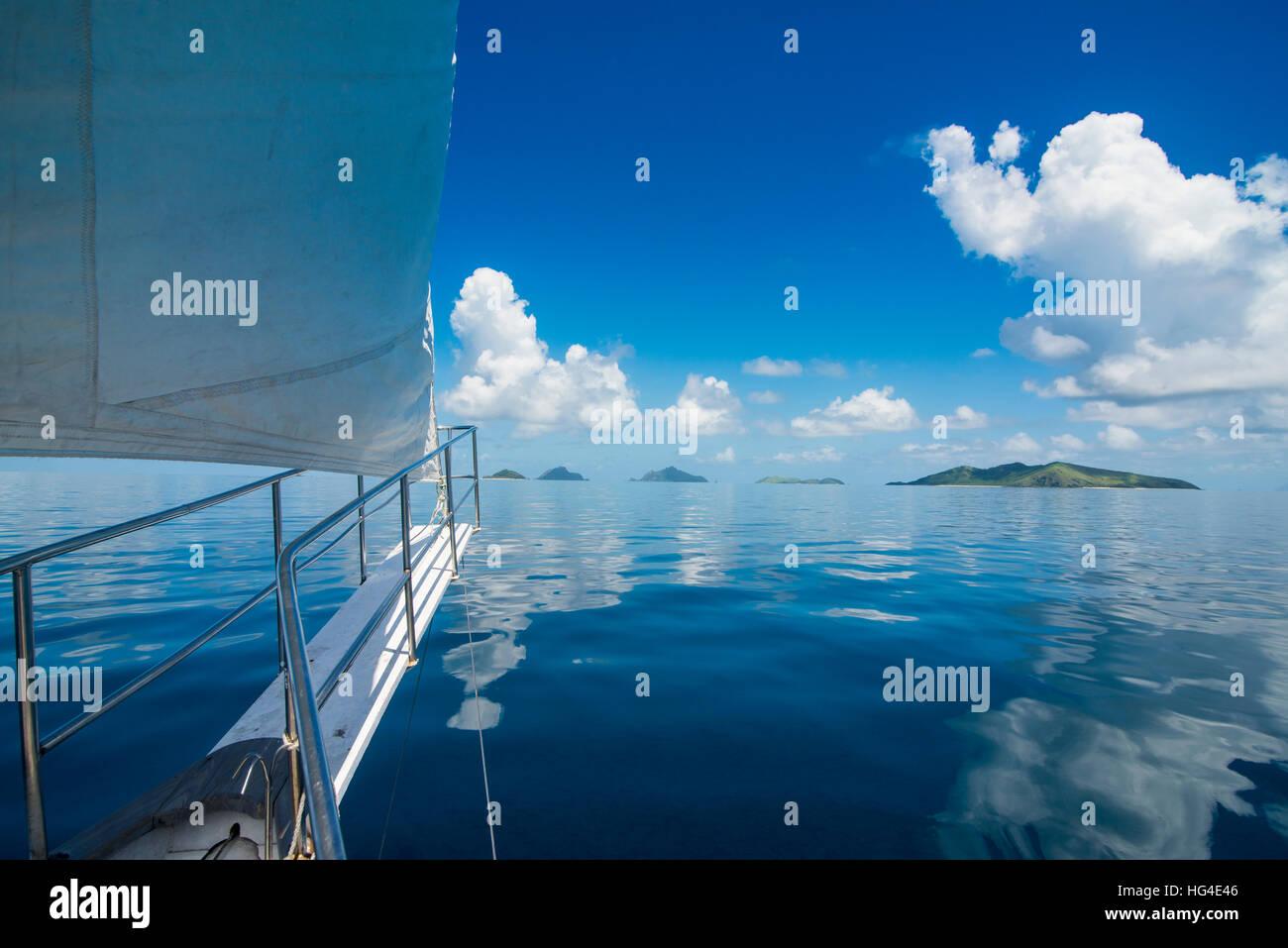 Barca a vela Nei molto piatte acque delle Isole Mamanuca, Figi e Sud Pacifico Immagini Stock