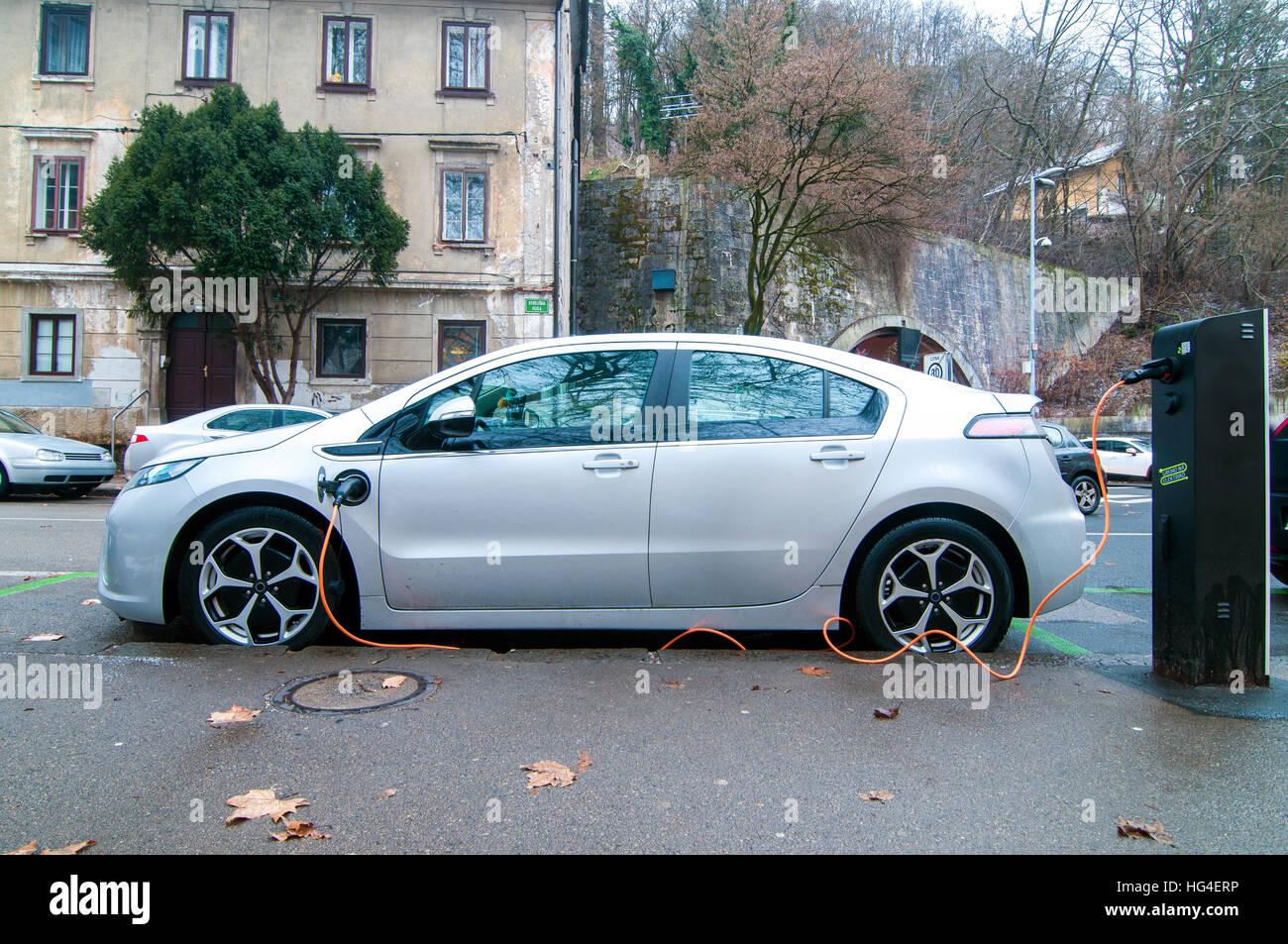 Auto elettrica, parcheggiata e la carica di una batteria Immagini Stock