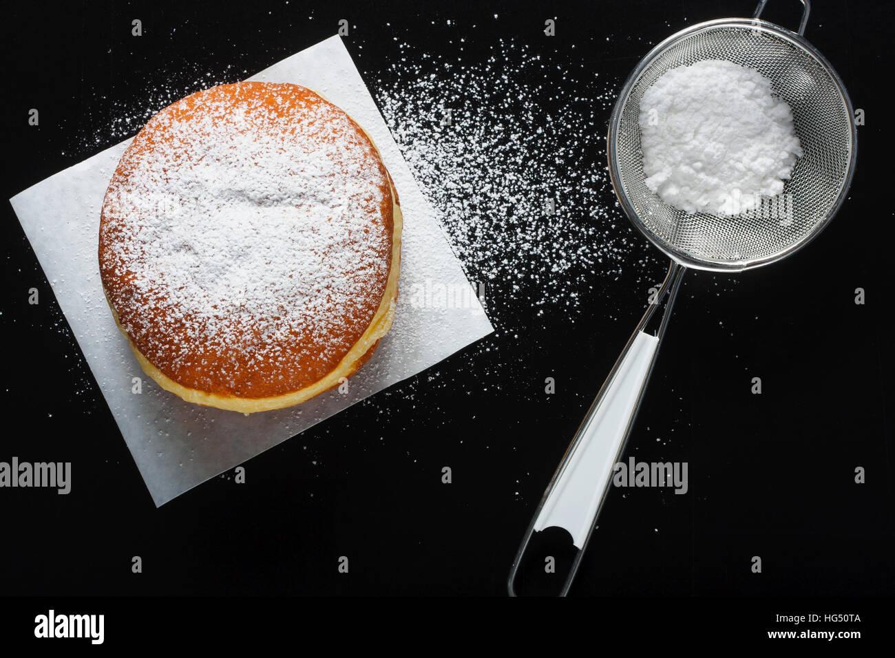 Donut e zucchero a velo su sfondo scuro Immagini Stock