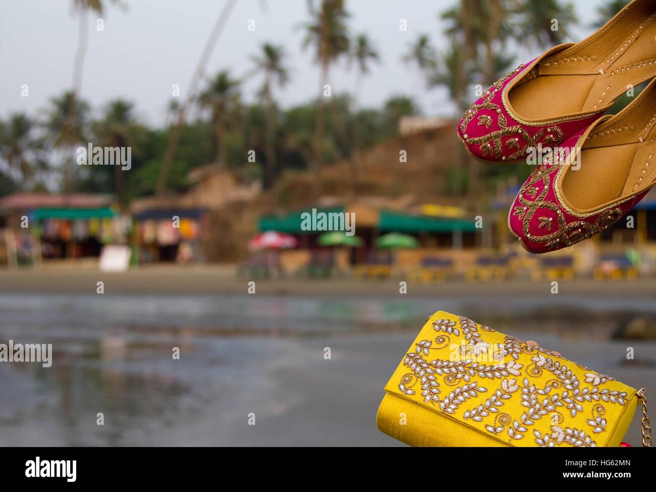 Coppia di tradizionale etnica indiana jutis rosa (scarpe donna) e una borsetta su una spiaggia in Goa, India con Immagini Stock
