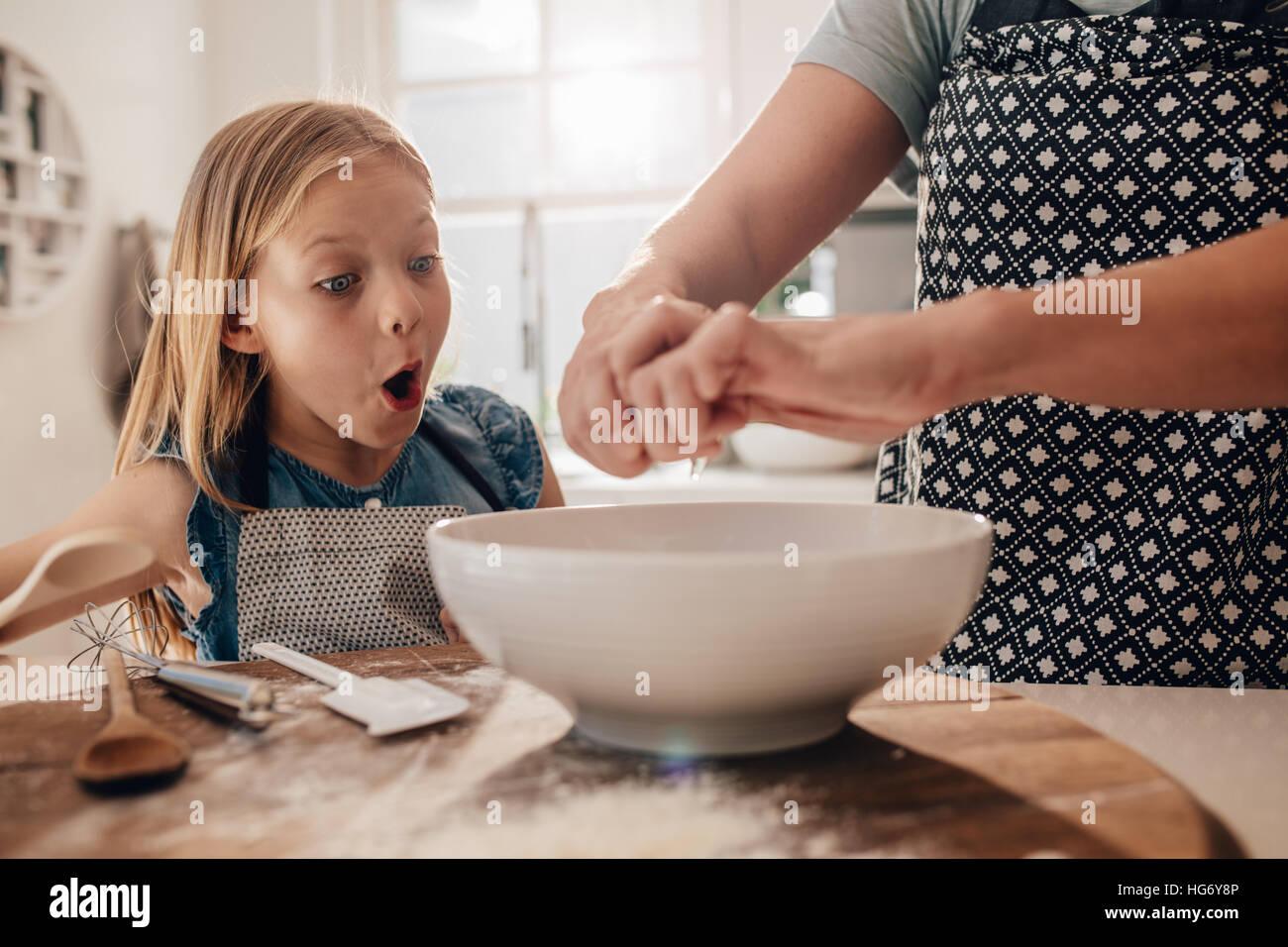 Eccitato ragazza giovane con la madre la preparazione di impasti per la cottura. La donna le mani per la cottura Immagini Stock