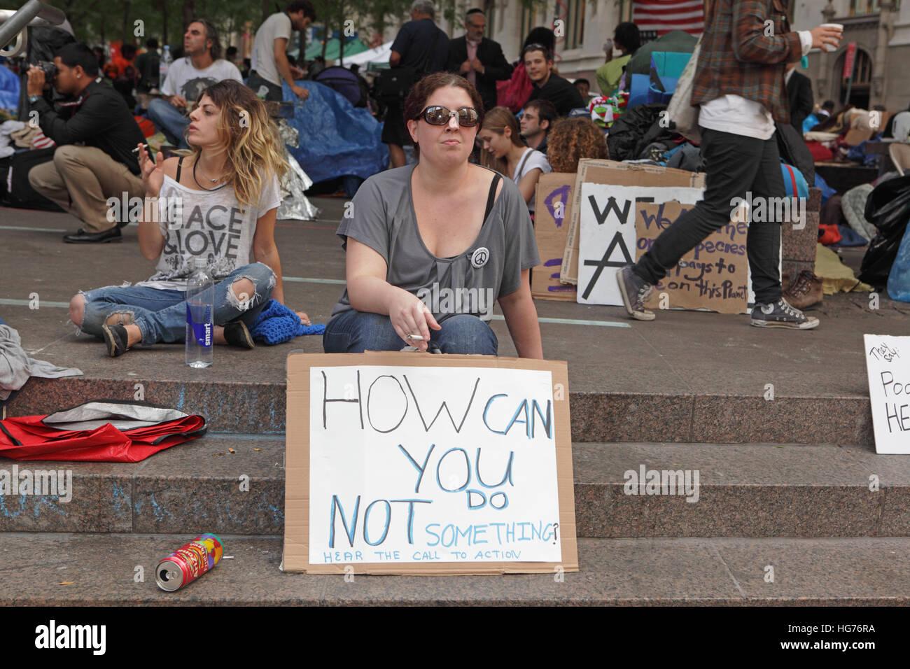 Occupare Wall Street protester camp a Zuccotti Park donna con una targhetta chiamando le persone in azione Immagini Stock