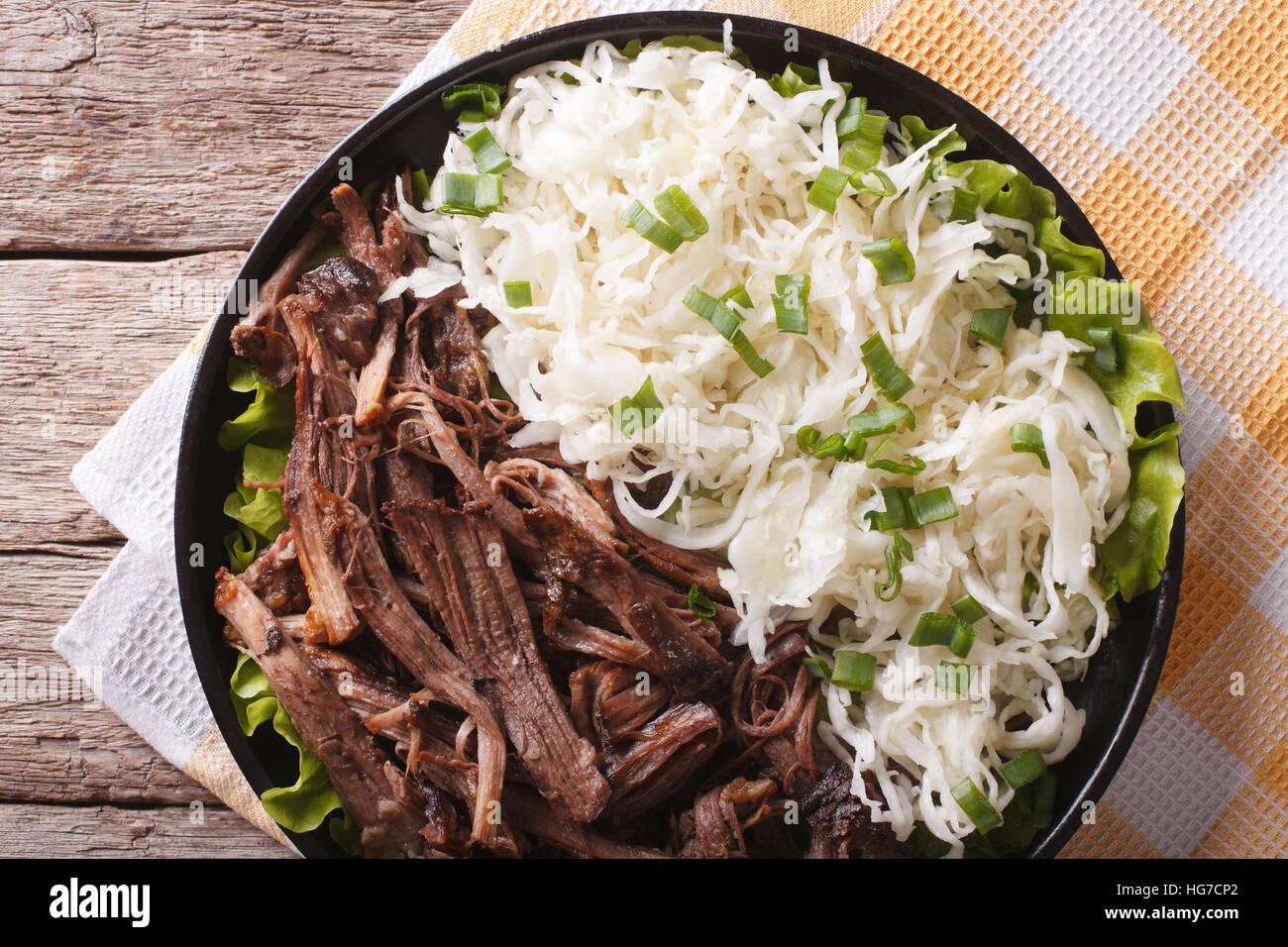 Gustosa tirato la carne di maiale e crauti close up su una piastra sul tavolo. orizzontale vista superiore Foto Stock