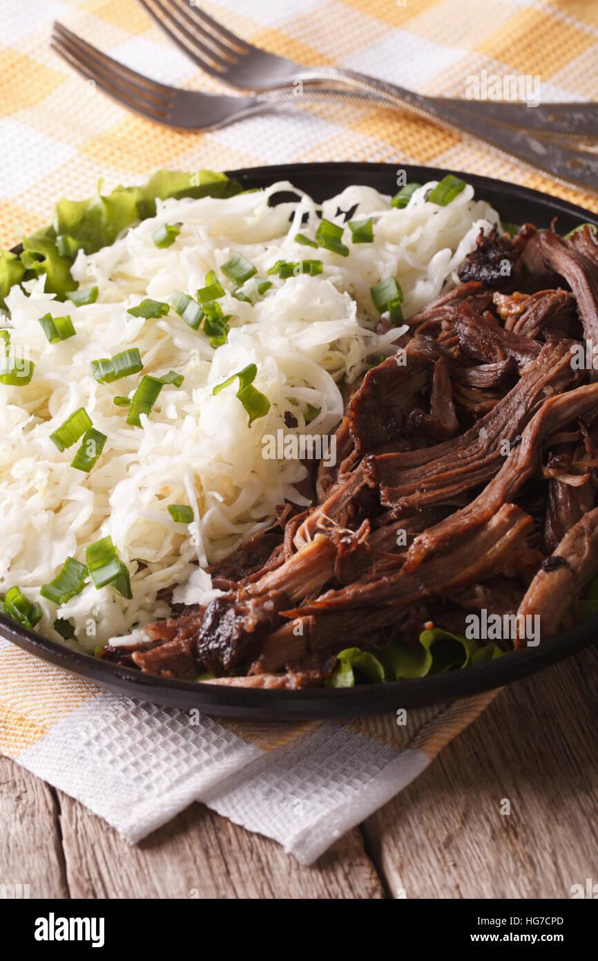 Tirate la carne di maiale con coleslaw close-up su una piastra sul piano verticale. Immagini Stock