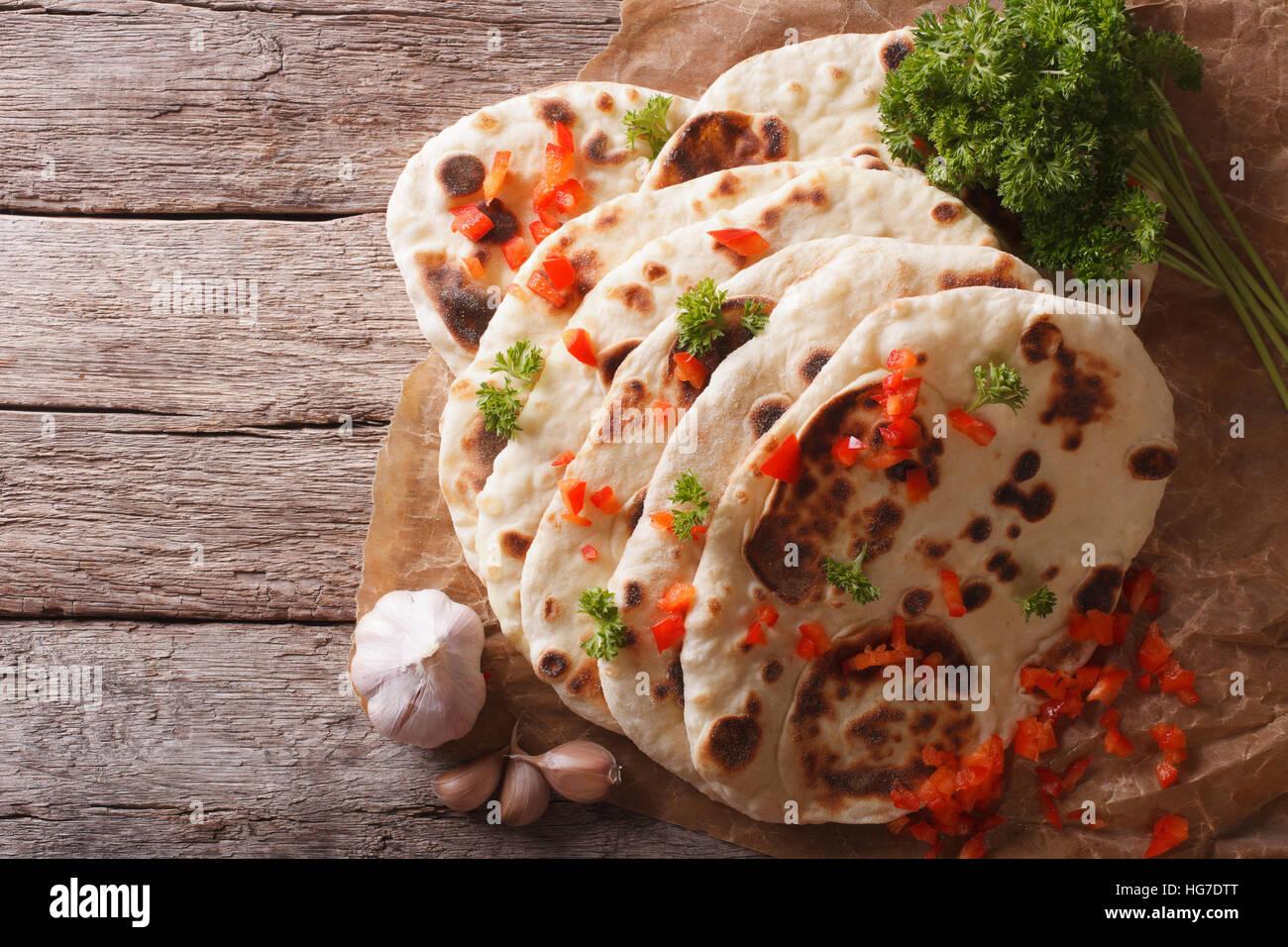 Naan indiano pane piatto con aglio ed erbe aromatiche sul tavolo. vista orizzontale dal di sopra Immagini Stock