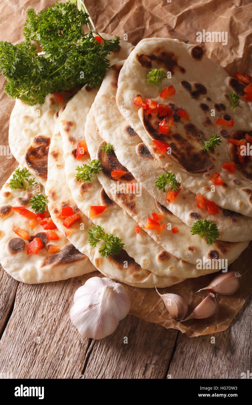 Naan indiano pane piatto con aglio ed erbe closeup sul tavolo. In verticale Immagini Stock