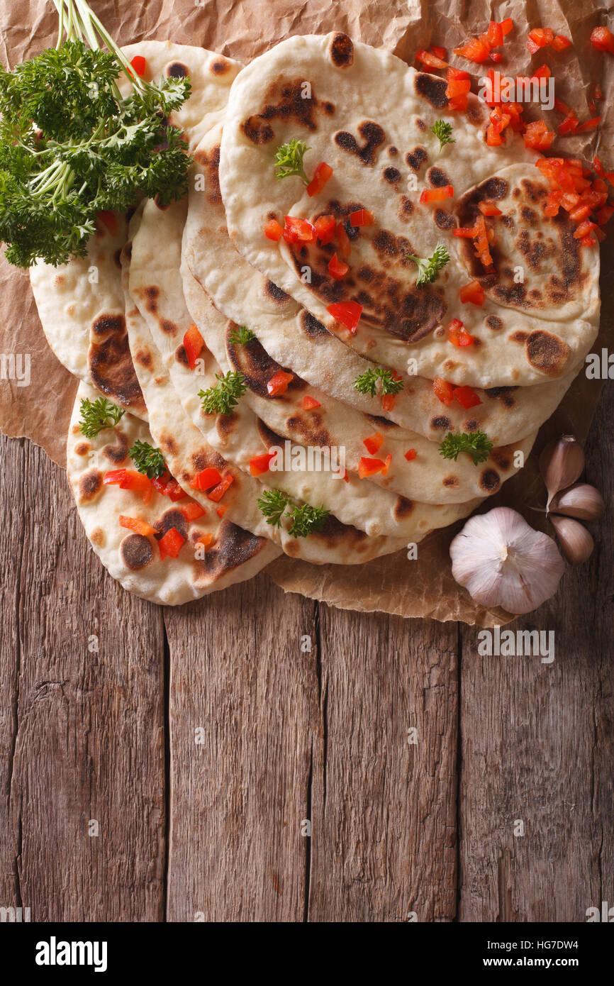 Naan indiano pane piatto con aglio ed erbe aromatiche sul tavolo. verticale vista superiore Immagini Stock