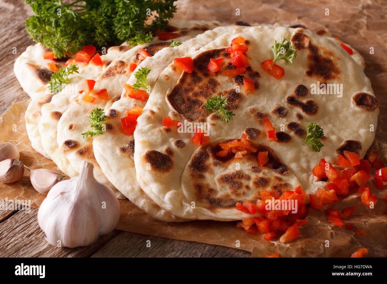 Naan indiano pane piatto con aglio e pepe macro sul tavolo. Posizione orizzontale Immagini Stock