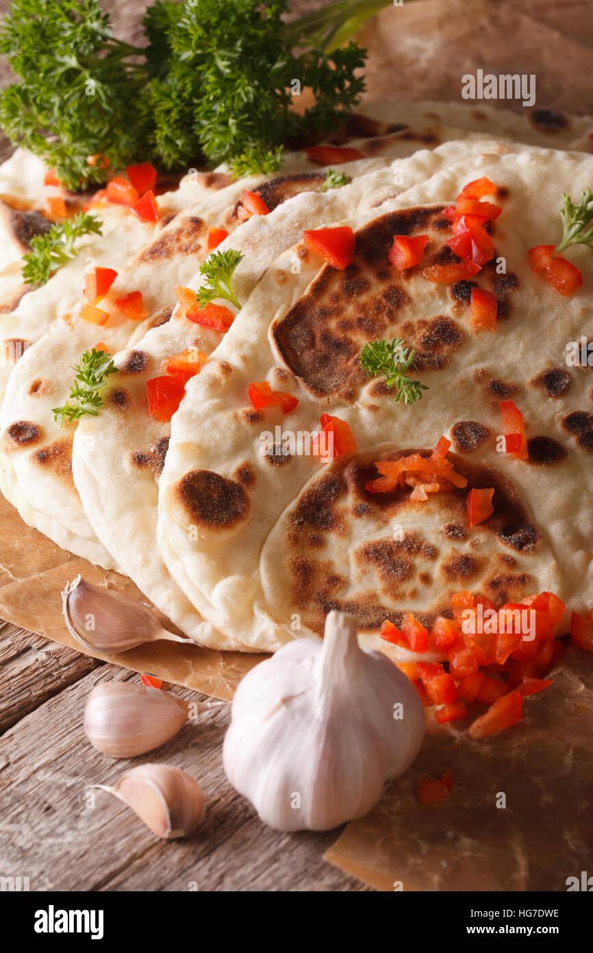 Naan indiano pane piatto con aglio e pepe macro sul piano verticale. Immagini Stock