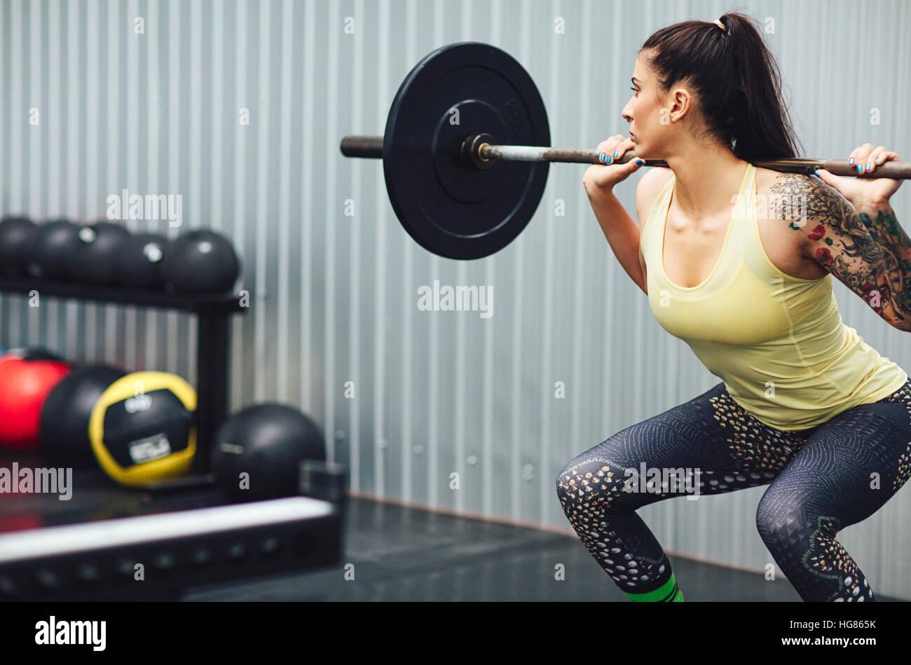 Donna con pesi barbell in palestra Immagini Stock