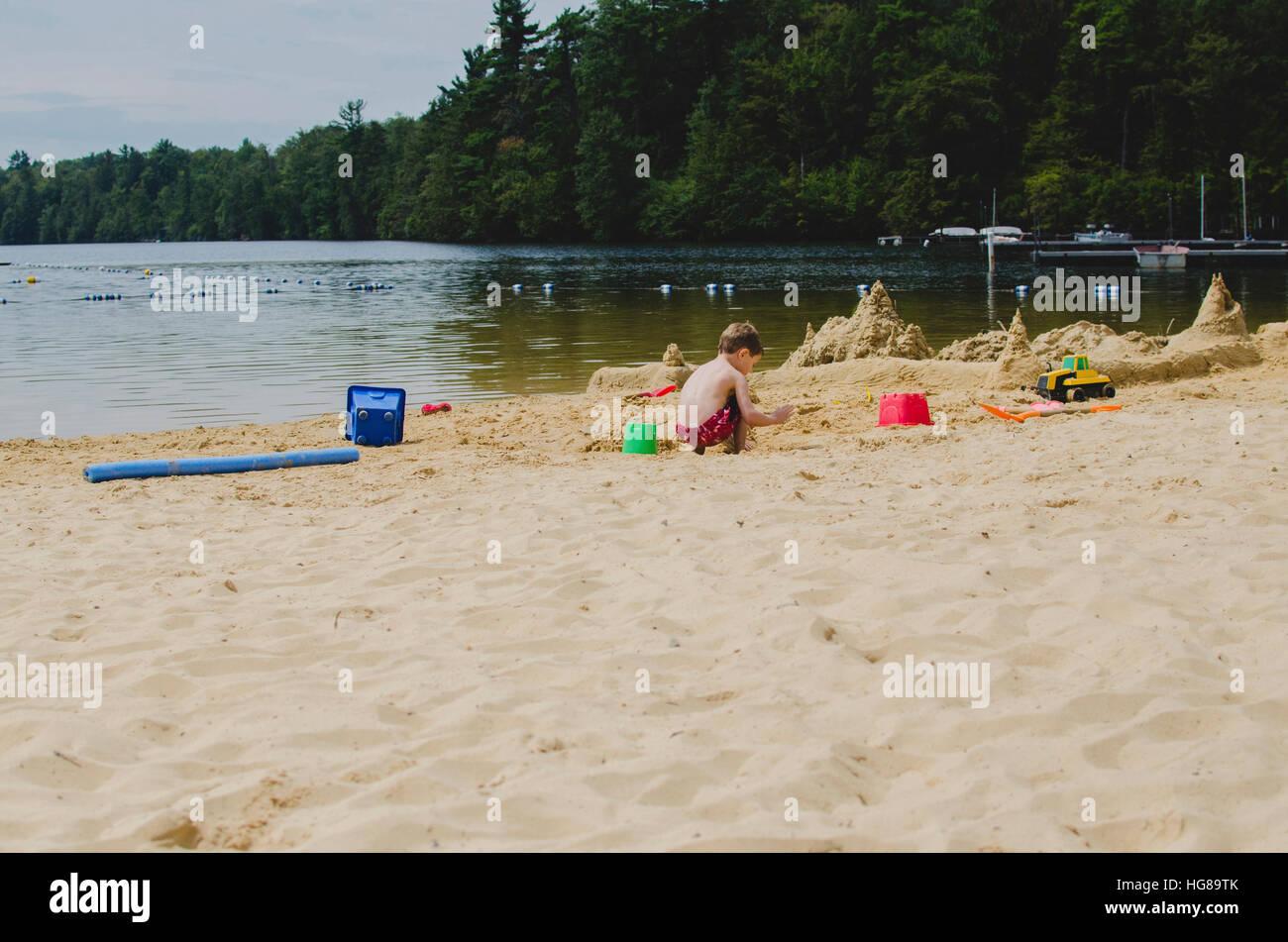 Vista posteriore del ragazzo giocando con i giocattoli mentre accovacciato sulla sabbia sul lungolago Immagini Stock