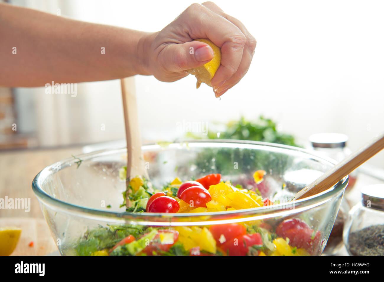 Close-up vista parziale della donna la spremitura di limone in ciotola con insalata di verdure Immagini Stock