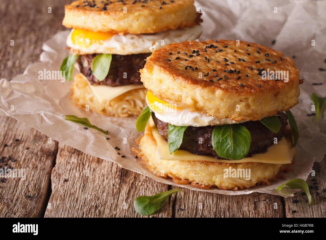 Il nuovo fast food: ramen burger close-up su un foglio di carta sul tavolo di legno orizzontale. Immagini Stock
