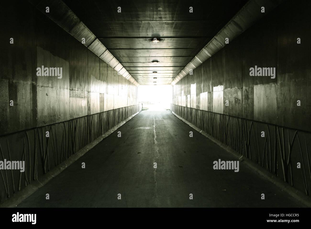 La luce alla fine del tunnel tunnel pedonale illuminato dalla luce del sole in uscita Foto Stock