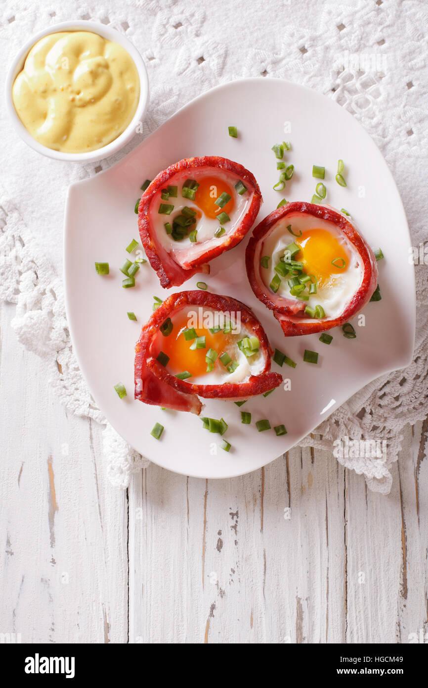 Uova fritte avvolto in pancetta croccante su una piastra con la salsa sul tavolo. verticale vista superiore Immagini Stock