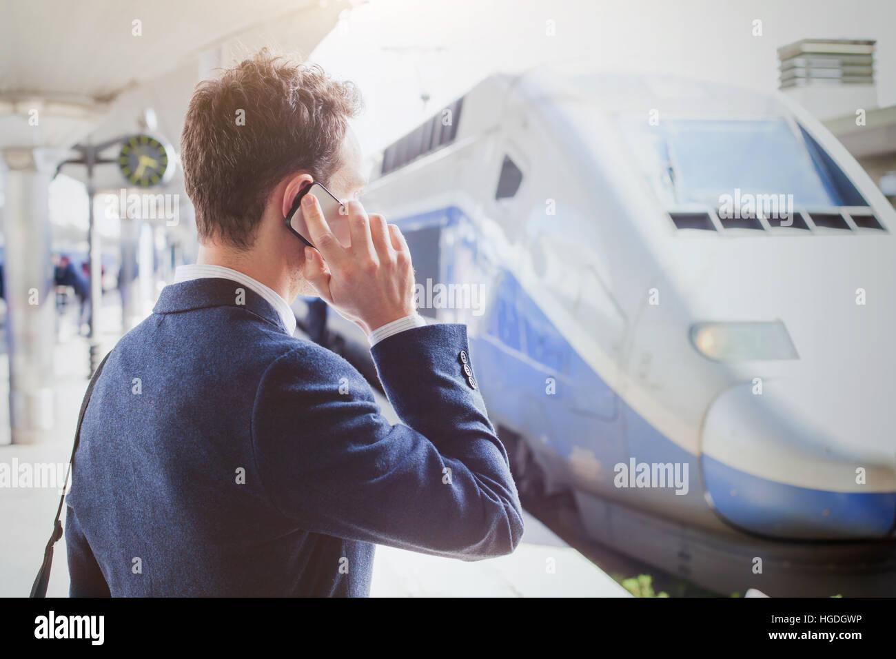 Business travel, imprenditore parla al telefono presso la stazione ferroviaria in attesa per il treno, mobile call Immagini Stock