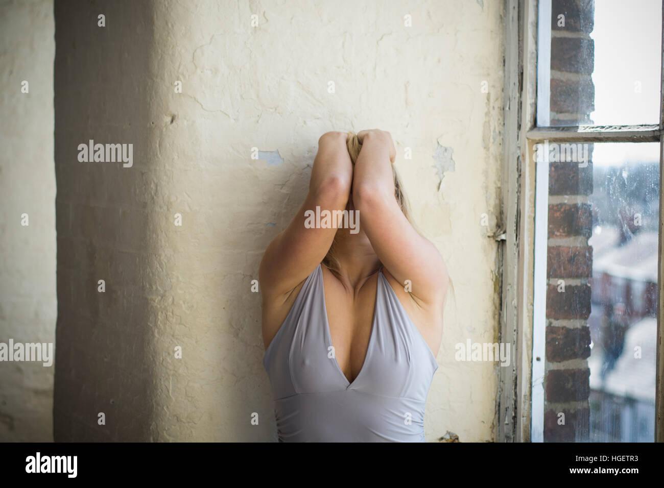 Ha sottolineato la donna in testa le mani dalla finestra Immagini Stock