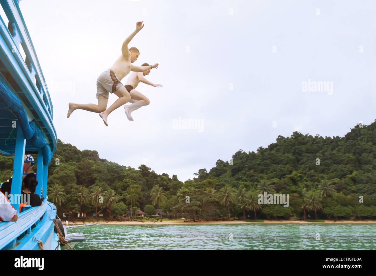 Amici jumping al mare dalla barca, divertirsi insieme, spiaggia avventura tropicale, adrenalina Immagini Stock
