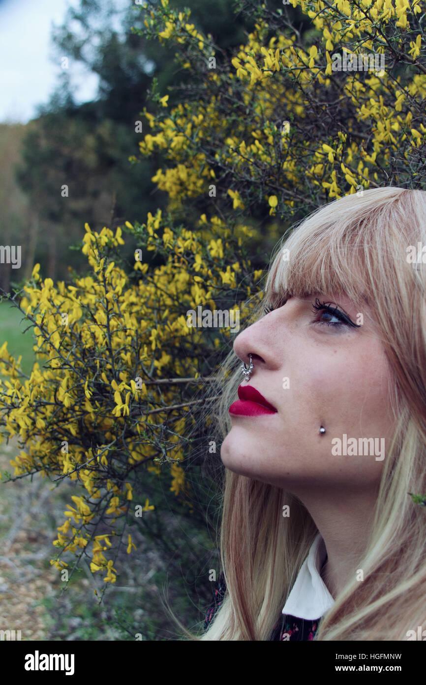 Giovane donna guarda nello spazio con un sacco di fiori gialli come sfondo Immagini Stock