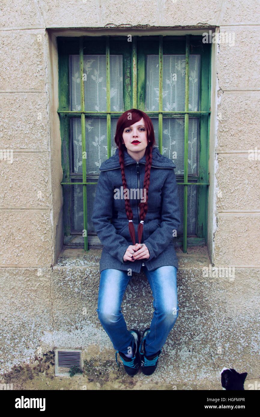 Giovane donna redhead, con due lunghe trecce seduto vicino a una finestra di vecchio Immagini Stock