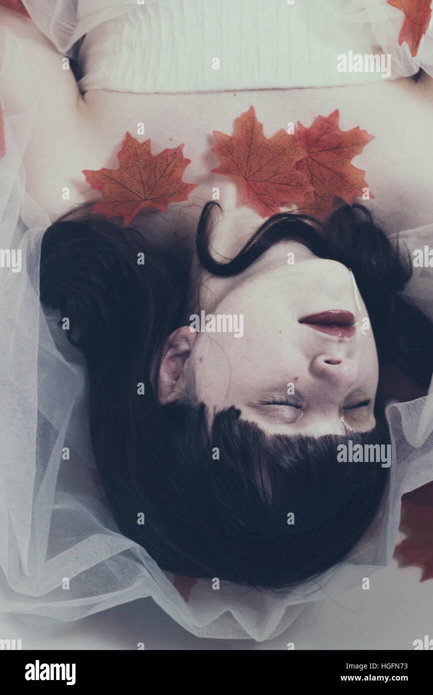 Bruna giovane donna sdraiata su acqua con un abito bianco e rosso di foglie di acero Immagini Stock