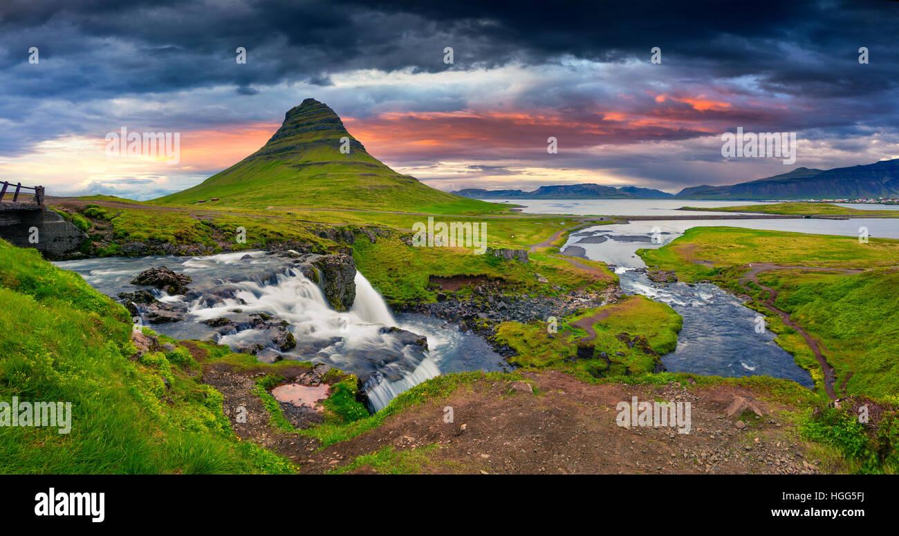 Estate tramonto sulla famosa cascata Kirkjufellsfoss Kirkjufell e montagna. Serata spettacolare panorama della penisola Foto Stock