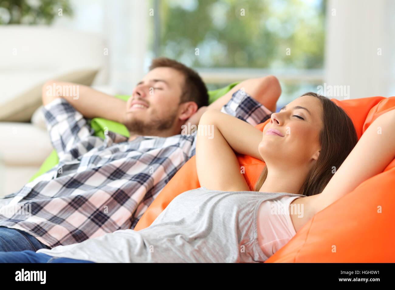 Coppia o coinquilini rilassarsi sdraiati su comodi pouf nel salotto di casa Immagini Stock