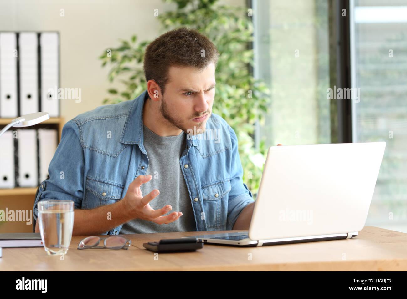 Arrabbiato libero professionista avendo problemi sulla linea con un notebook in un desktop accanto a una finestra Immagini Stock