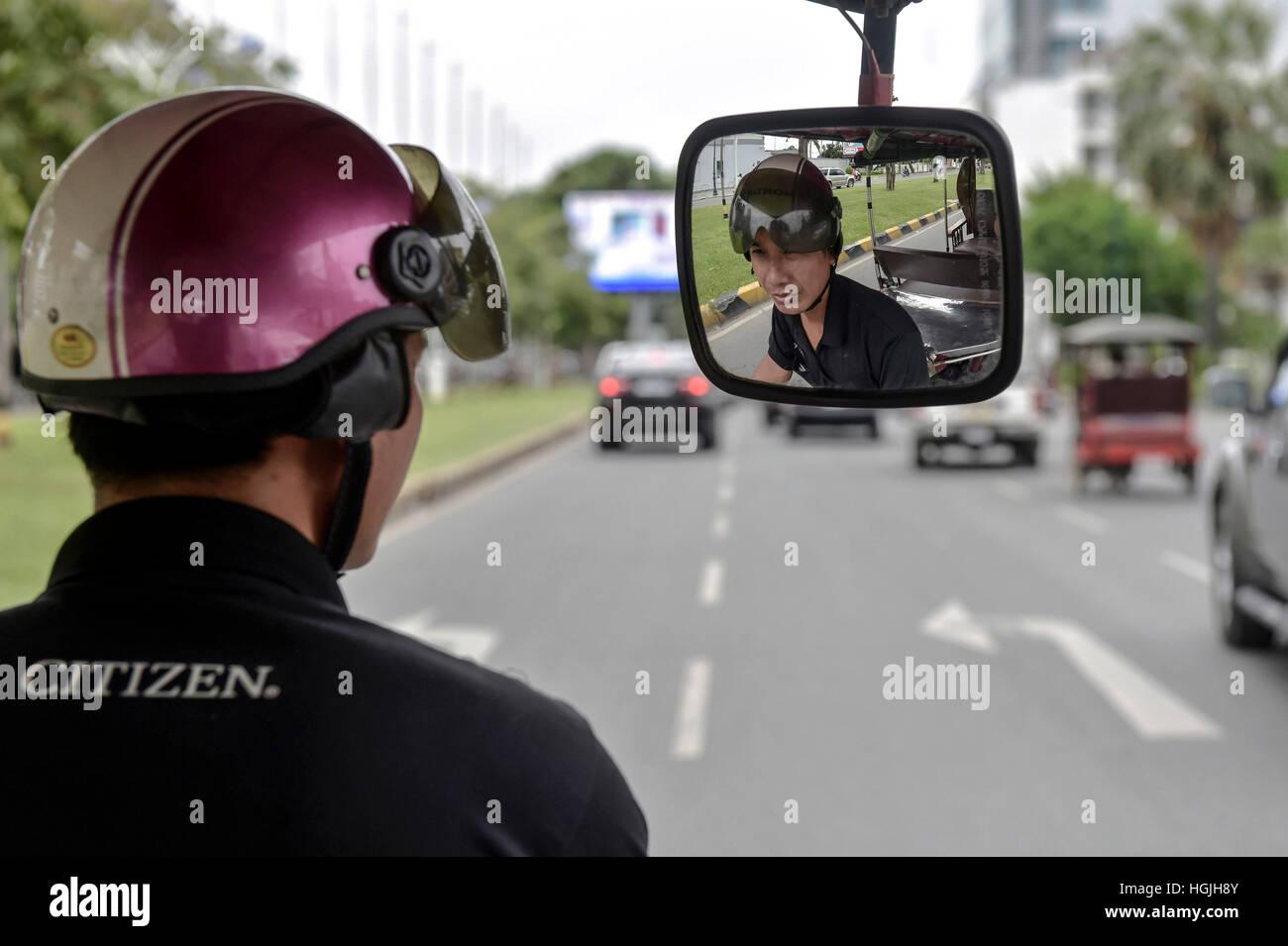 Un Tuk Tuk driver con casco Guardando nello specchietto retrovisore, Phnom Penh Cambogia Immagini Stock