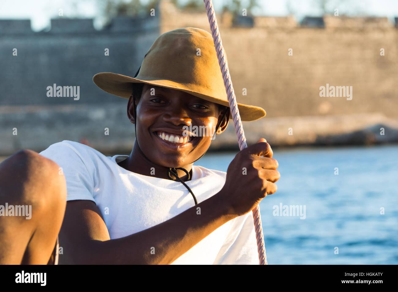 Giovane uomo su un dhow davanti al forte, Isola di Mozambico (Ilha de Mocambique), Mozambico Immagini Stock