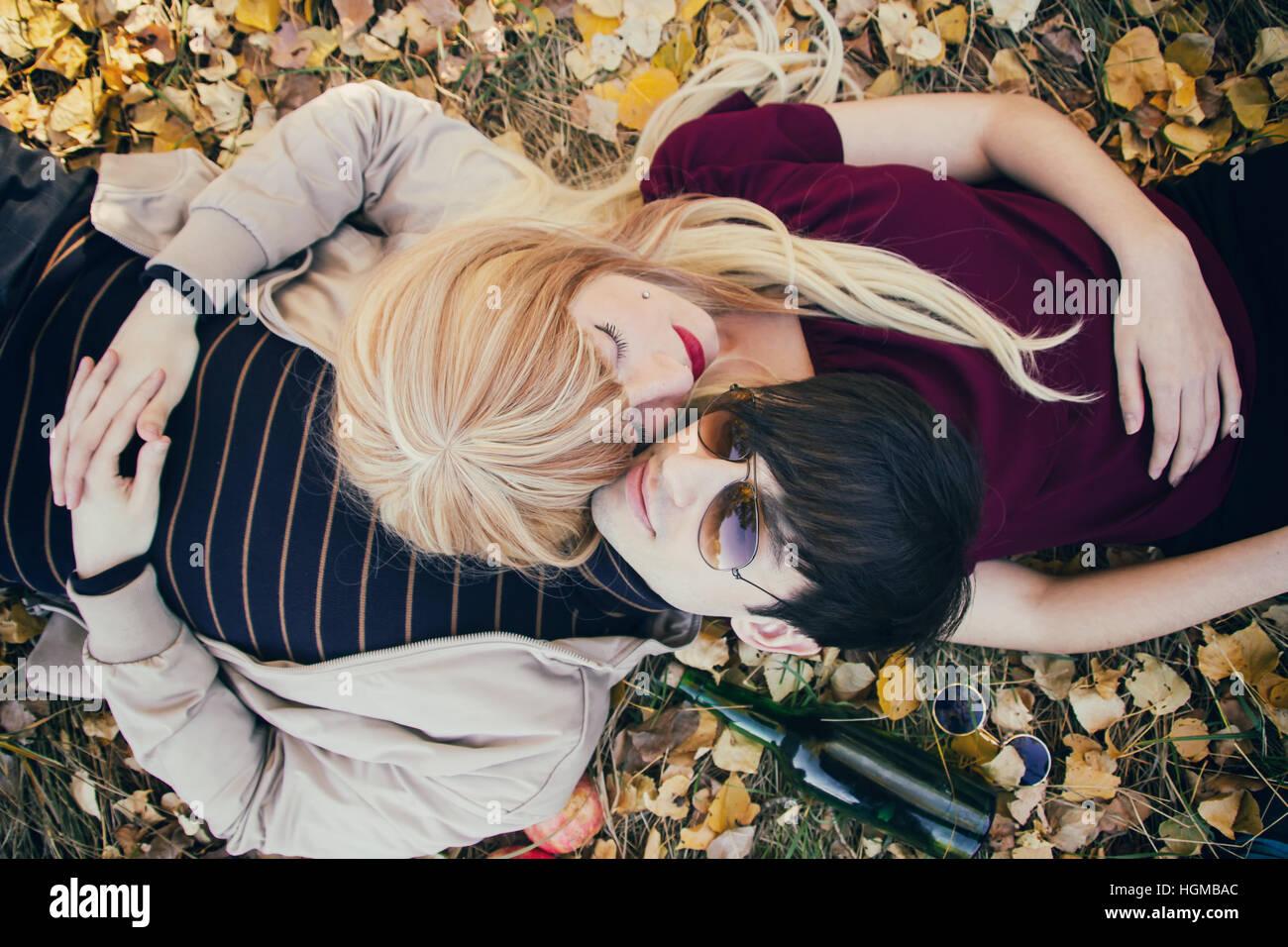 Coppia giovane sdraiato sul pavimento in un parco in autunno Immagini Stock