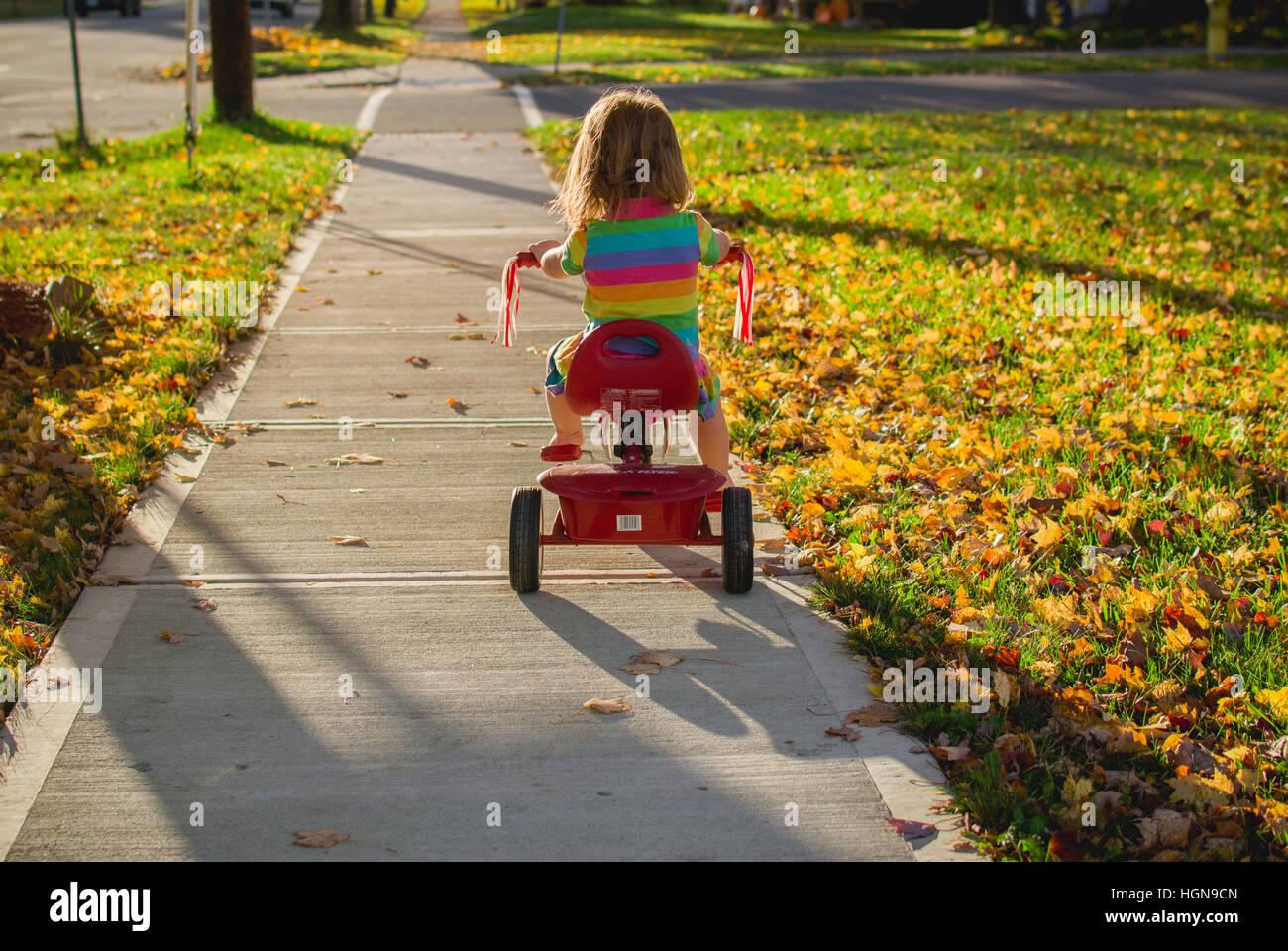 Una giovane ragazza cavalca un triciclo in una piccola città negli stati uniti. Immagini Stock