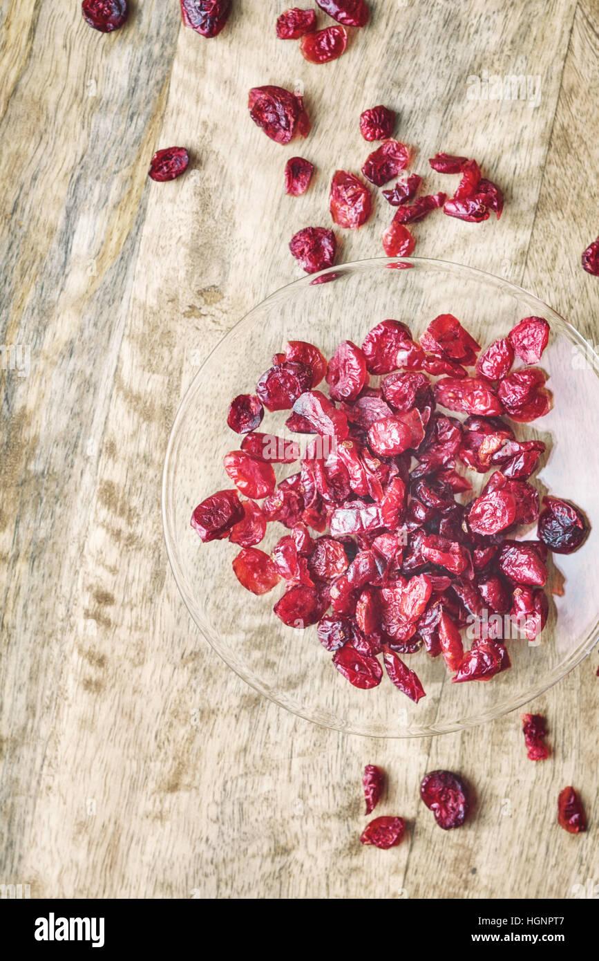 Mirtilli rossi secchi nel recipiente di vetro sul tavolo di legno Immagini Stock